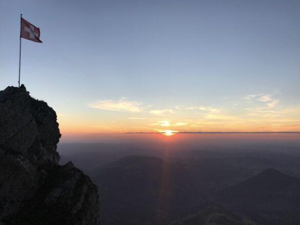 Sonnenuntergang mit Schweizer Fahne bei der Tierwis